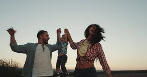 Glimlachende mooie jonge familie, drie leden, mammapapa en hun babyzoon het gelukkige lopen door het gebied bij zonsondergang stock videobeelden