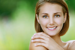 Glimlachende mooie jonge vrouw dicht Stock Afbeeldingen