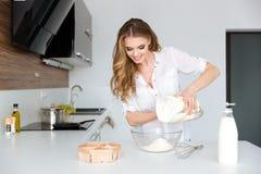 Glimlachende mooie jonge vrouw die deeg op de keuken voorbereiden Royalty-vrije Stock Foto