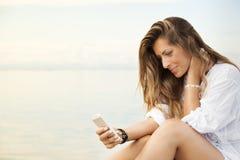 Glimlachende mooie jonge vrouw die een mobiele telefoon met behulp van Royalty-vrije Stock Foto's