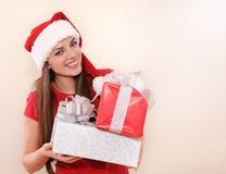 Glimlachende mooie jonge vrouw in Kerstmanhoed met giften voor Kerstmis Stock Foto