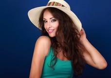 Glimlachende mooie jonge vrouw in strohoed met lang krullend haar royalty-vrije stock fotografie