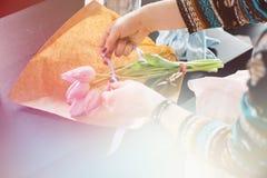 Glimlachende mooie jonge vrouwenbloemist die installaties in bloemwinkel schikken, het lichte stemmen stock afbeeldingen