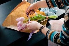 Glimlachende mooie jonge vrouwenbloemist die installaties in sh bloem schikken stock foto