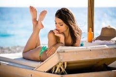 Glimlachende mooie vrouw die in een bikini op een strand bij tropische reistoevlucht zonnebaden, die de zomer van vakantie geniet Royalty-vrije Stock Fotografie