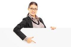 Glimlachende mooie vrouw die in kostuum op een leeg paneel richten Royalty-vrije Stock Afbeeldingen