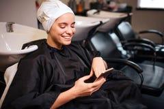 Glimlachende mooie vrouw die met handdoek op hoofd telefoon bekijken alvorens kapsel te doen Hair spa in schoonheidssalon stock afbeeldingen
