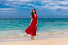 Glimlachende mooie vrouw in een rode kleding die zich op overzeese coas bevinden Royalty-vrije Stock Foto