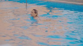 Glimlachende mooie vrouw en haar leuk kind in de pool stock footage