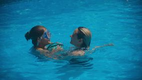 Glimlachende mooie vrouw en haar leuk kind in de pool Moeder die haar leren te zwemmen weinig dochter stock footage