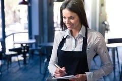 Glimlachende mooie vrouwelijke kelner in schort stock afbeelding