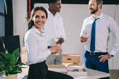 glimlachende multi-etnische collega's die koffiepauze in nieuw bureau hebben royalty-vrije stock foto's