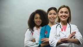 Glimlachende multiraciale artsen met rode linten, internationaal AIDS-voorlichtingsteken stock videobeelden