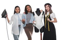 Glimlachende naaisters die kleermakershulpmiddelen houden terwijl het werken met witte bodysuit aan model royalty-vrije stock foto