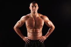 Glimlachende naakte chested mannelijke lichaamsbouwer met handen op heupen Stock Afbeeldingen