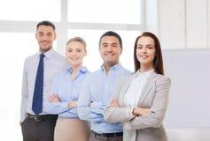 Glimlachende onderneemster in bureau met team op rug Stock Afbeeldingen