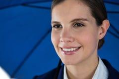Glimlachende onderneemster die blauwe paraplu houdt Royalty-vrije Stock Afbeeldingen