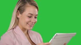 Glimlachende onderneemster die een tabletcomputer op het groen scherm, chromasleutel met behulp van stock videobeelden