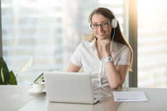 Glimlachende onderneemster die hoofdtelefoons met laptop het stellen dragen bij w royalty-vrije stock foto's