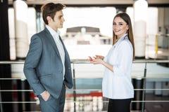 Glimlachende onderneemster die iets vertellen aan haar collega in het bureau De bedrijfsman spreekt met bedrijfsvrouw in bureau stock foto's