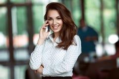 Glimlachende onderneemster die op de telefoon op het kantoor spreken stock fotografie