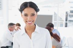 Glimlachende onderneemster en haar collega's Royalty-vrije Stock Afbeeldingen