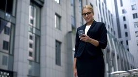 Glimlachende onderneemster gelukkig om bericht op smartphone met goed nieuws te lezen, salaris stock afbeeldingen