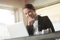 Glimlachende onderneemster met laptop stock foto's