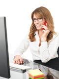 Glimlachende onderneemster op de telefoon in bureau Stock Afbeeldingen