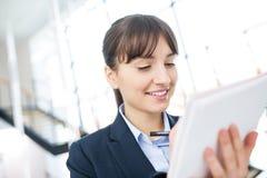 Glimlachende Onderneemster Writing On Document in Bureau royalty-vrije stock afbeeldingen
