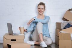 glimlachende ondernemer met koffie gaan zittend op vloer royalty-vrije stock afbeeldingen