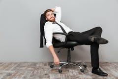 Glimlachende ontspannen zakenman die als bureauvoorzitter rusten stock foto