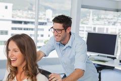 Glimlachende ontwerpers die op een draaistoel spelen Royalty-vrije Stock Afbeeldingen