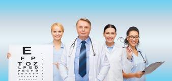 Glimlachende oogartsen en verpleegsters Stock Foto's