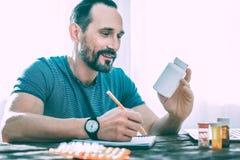 Glimlachende opgewekte mens die nota's over sommige pillen maken royalty-vrije stock afbeeldingen