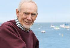Glimlachende oude mens door het overzees Stock Fotografie
