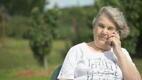 Glimlachende oude vrouw die gebruikend een mobiele telefoon spreken stock videobeelden
