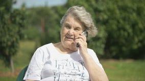 Glimlachende oude vrouw die gebruikend een mobiele telefoon spreken stock video
