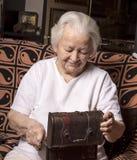 Glimlachende oude vrouw met kist Stock Afbeelding