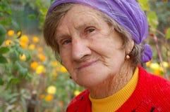 Glimlachende oude vrouw in veel-gekleurde bovenkleding Royalty-vrije Stock Foto's