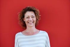Glimlachende oudere vrouw met krullend haar tegen rode muur stock foto