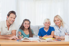 Glimlachende ouders die hun kinderen met hun thuiswerk helpen Stock Fotografie