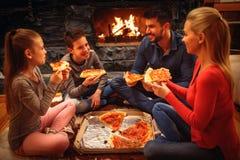 Glimlachende ouders en kinderen die pizza op de vloer eten Royalty-vrije Stock Afbeelding