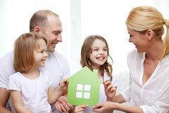 Glimlachende ouders en twee meisjes bij nieuw huis stock afbeelding
