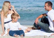Glimlachende ouders met hun zoonszitting op het zand Royalty-vrije Stock Afbeelding