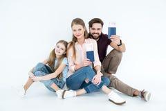 Glimlachende ouders met paspoorten en kaartjes en dochter met tablet royalty-vrije stock foto's