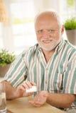 Glimlachende oudste die medicijn neemt Stock Foto