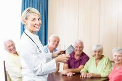 Glimlachende oudsten en verpleegster die een tablet houden royalty-vrije stock foto