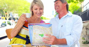 Glimlachende paar het drinken koffie en het controleren van de kaart stock footage