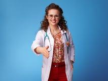 Glimlachende pediater arts die hand voor handdruk op blauw geven royalty-vrije stock afbeelding